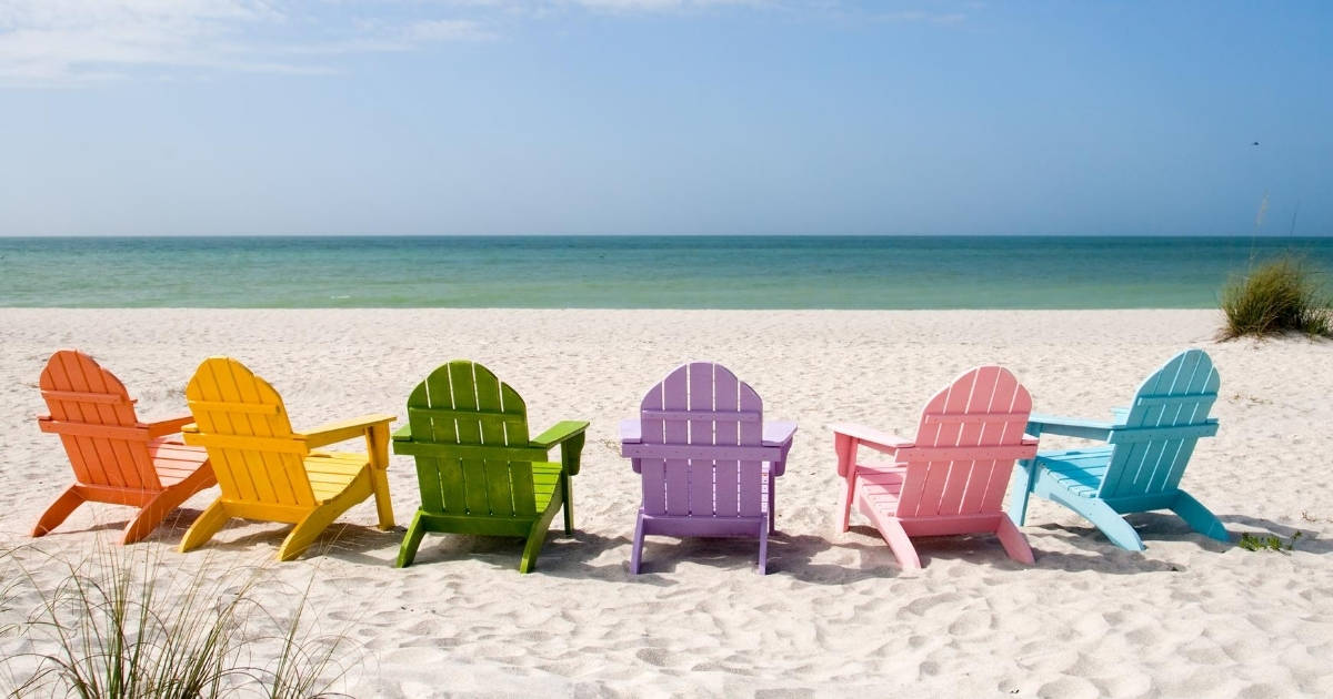 colorful beach chairs on the beach facing the ocean
